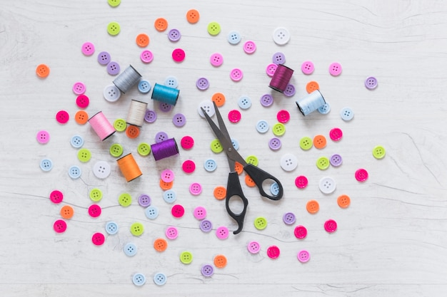 Spool and scissor on spread colorful buttons over white textured background
