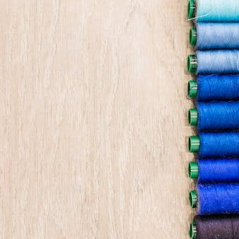 Spool of threads in row on wooden background