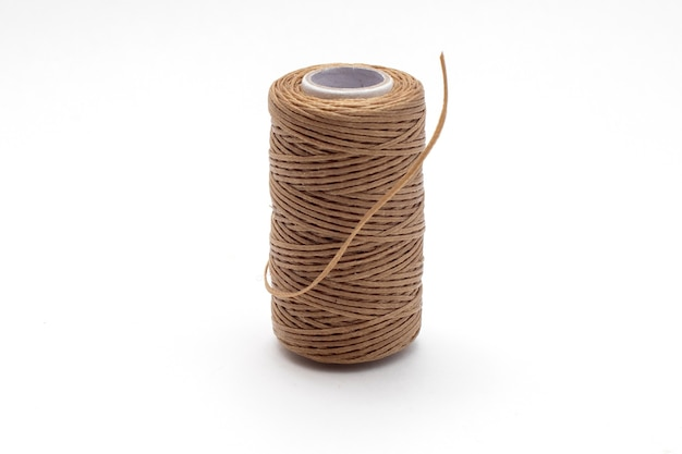 Spool of waxed brown sewing threads.