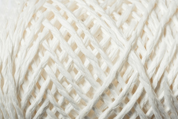 Spool of white linen rope, textured background