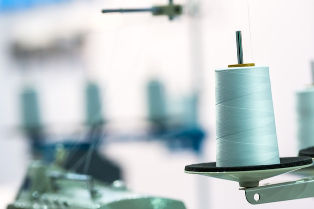 Spool of white threads on sewing machine, closeup