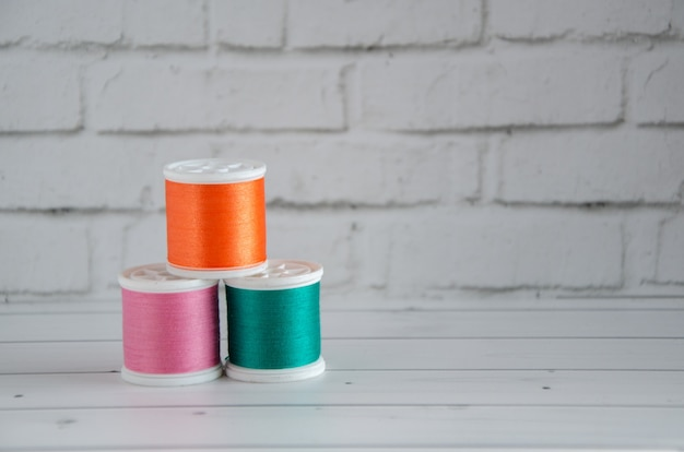 Spools of colored thread on a light background of a workspace and a brick wall. concept: needlework, sewing, hand-made. space for text