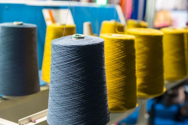 カラースレッドのクローズアップ、縫製機器のスプール。布工場、製織、繊維生産、衣料産業