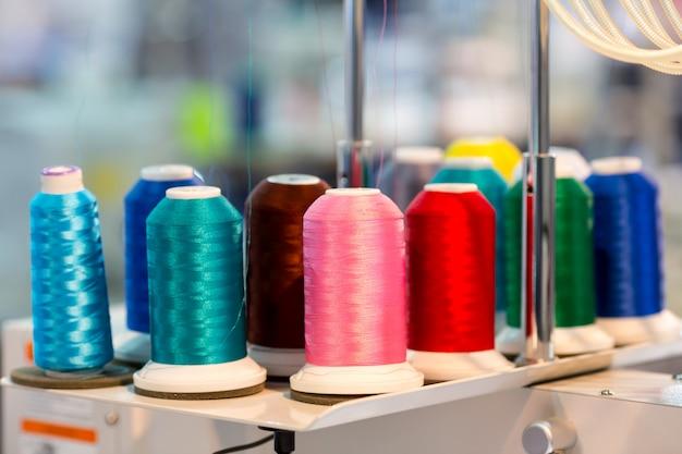 Катушки цветных ниток крупным планом, швейный материал. тканевая фабрика, ткачество, текстильное производство, швейная промышленность