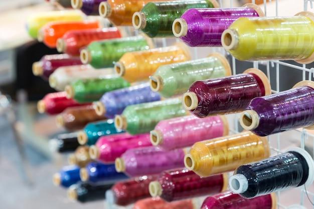 新しい糸のクローズアップ、裁縫用具のスプール。布工場、製織、繊維生産、衣料産業