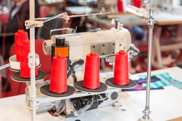 ミシンの赤い糸のスプール。布工場、製織、繊維生産、衣料産業