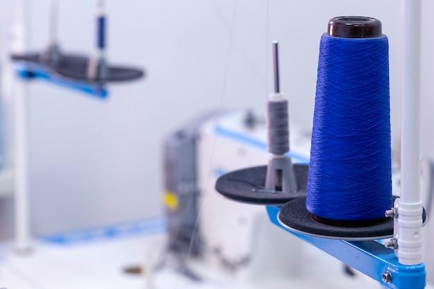 縫製工場での糸のスプールとミシン。縫製機器、中小企業。