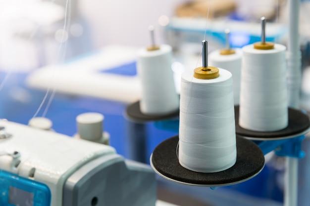 ミシン、クローズアップの白い糸のスプール。布工場、製織、繊維生産、衣料産業