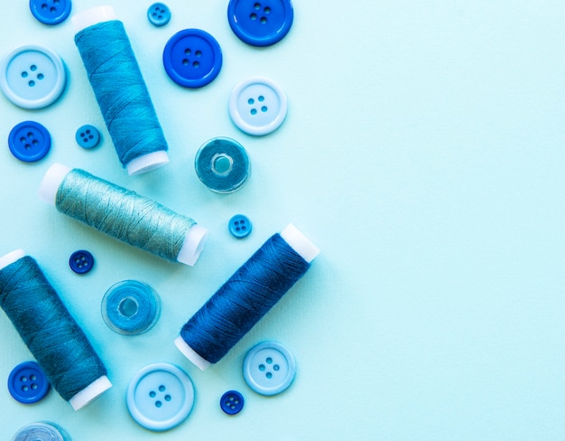 Spools of thread and buttons in blue tones on blue, flat lay