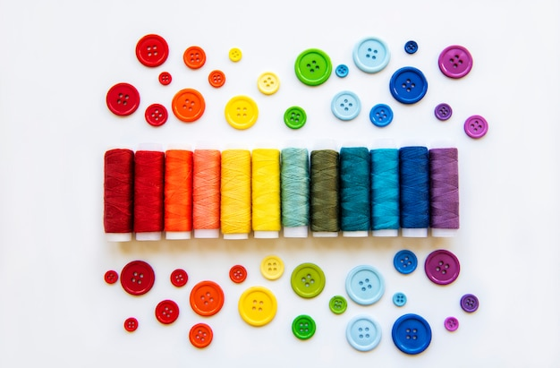 Spools of thread and buttons on the colors  of the rainbows