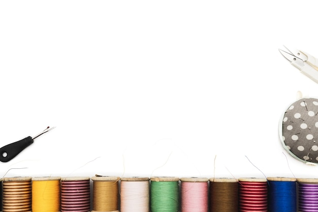 Spools of threads lined up against white background , view from above
