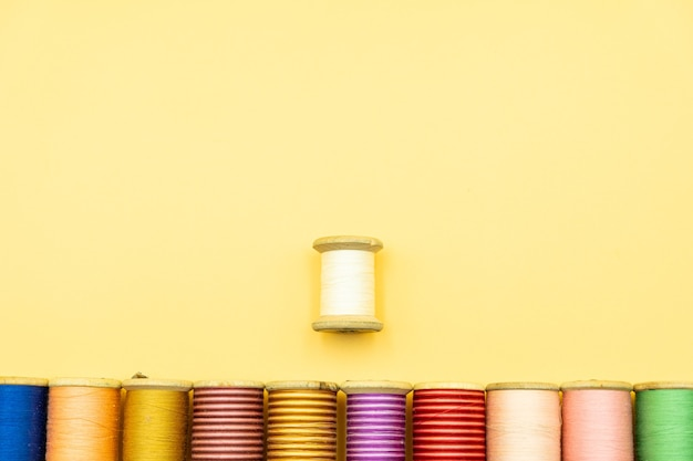 Spools of threads lined up against yellow background , view from above