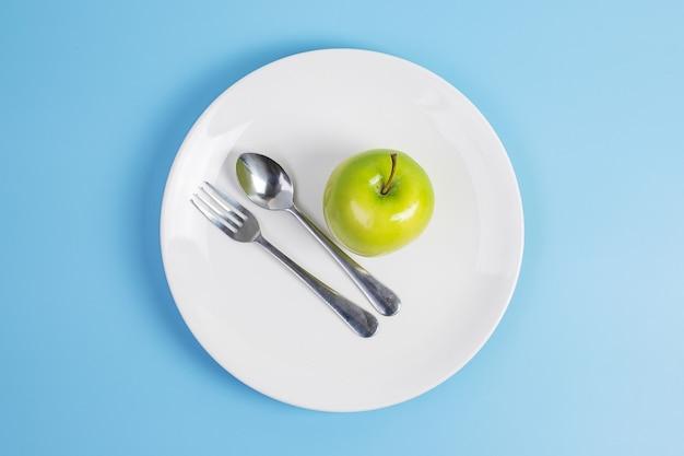 Ложка и вилка, зеленое яблоко на белой керамической тарелке на синем фоне