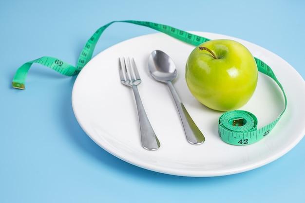Ложка и вилка, зеленое яблоко на белой керамической тарелке с зеленой измерительной лентой на синем фоне