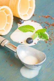 青い木製のテーブルの上の円錐形のスプーンと溶けたバニラアイスクリーム