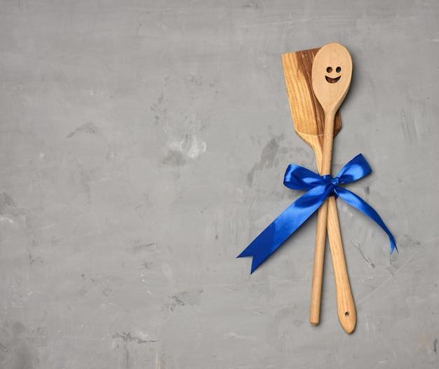 灰色の背景、上面図に青いリボンで結ばれたスプーンとヘラ