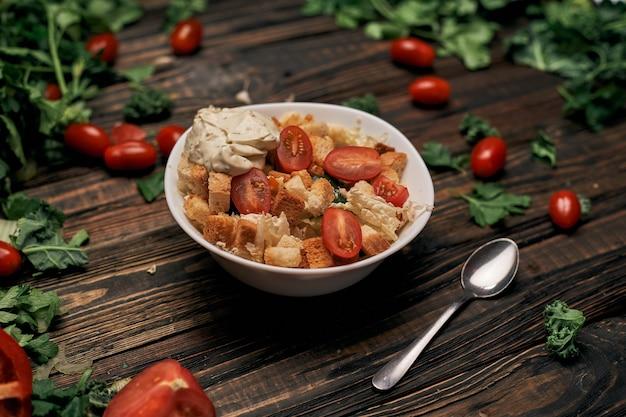 Ложка и овощной салат с крекерами на столе