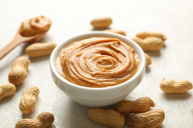 Spoon and bowl with peanut butter, and peanuts on white background