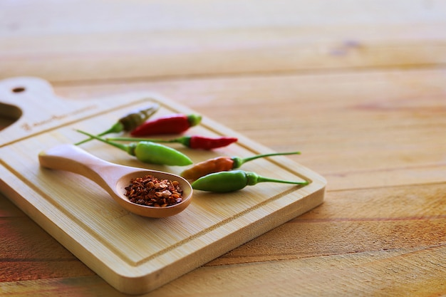 Spoon of cayenne pepper and fresh chilli on wood