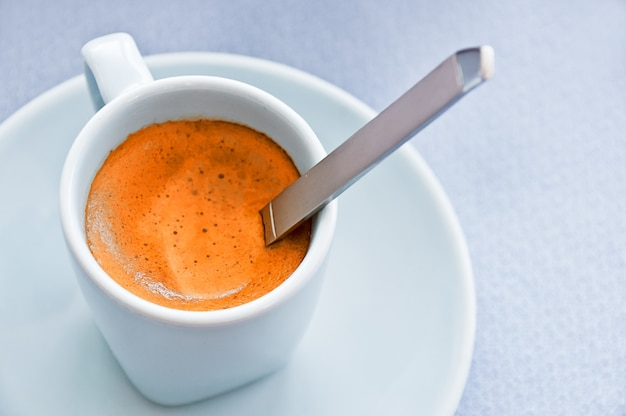 Spoon in a cup of espresso coffee