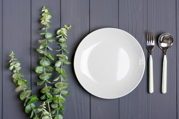 Spoon, fork, grey plate and sprig of green eucalyptus on gray wooden table