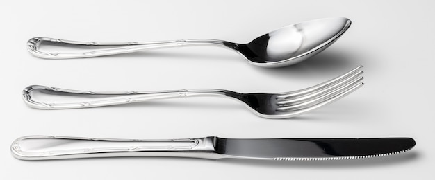 Spoon, fork and knife on a white background