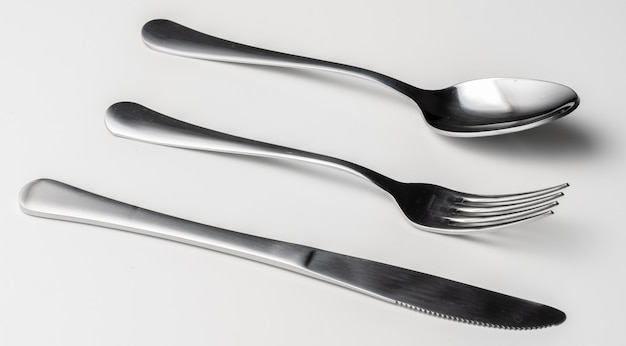 Spoon, fork and knife on a white surface