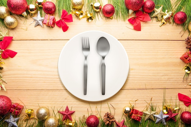 Spoon and fork on the plate with christmas ornaments