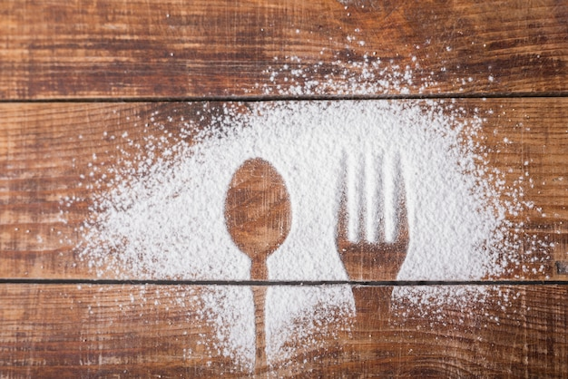 Spoon and fork shape on sugar powder over the wooden desk