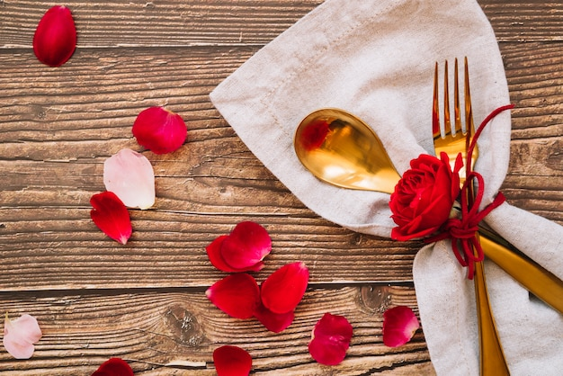Spoon and fork with red flower on napkin near petals