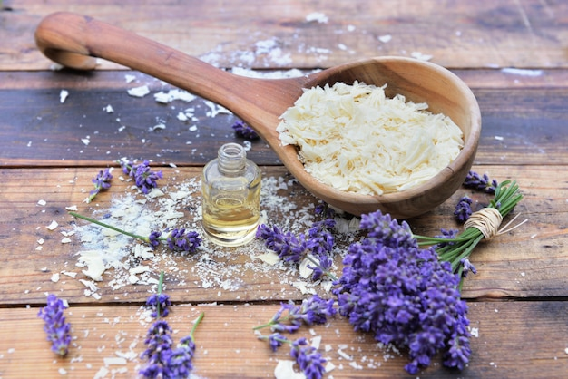 Spoon full of flakes of soap with essential oil and bunch od lavender flowers on wooden background