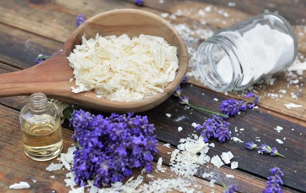Ложка, полная хлопьев мыла с эфирным маслом и букетом цветов лаванды и бикарбонатом натрия на деревянном фоне