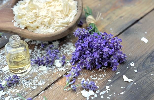 エッセンシャルオイルと木製の背景にラベンダーの花の束と石鹸のフレークのスプーン