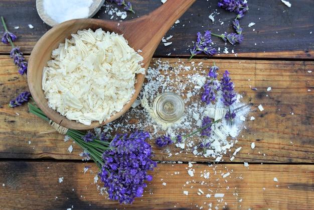Ложка, полная хлопьев мыла с эфирным маслом и букетом лаванды на деревянном фоне