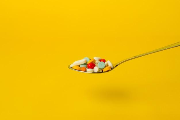노란색 바탕에 알 약의 가득 차있는 숟가락. 자기 치료 및 약물 남용 개념.