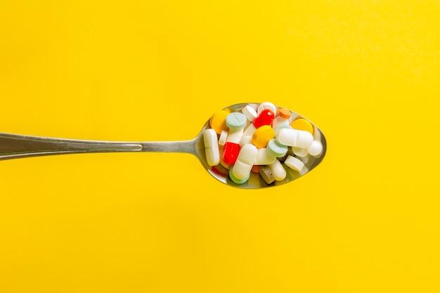Ложка полная таблеток на желтом фоне.