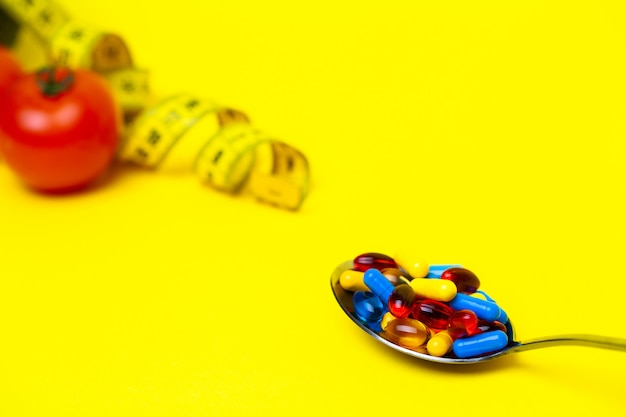 Spoon full of pills for weight loss on yellow.