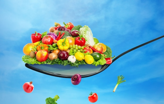 Spoon full of various fruit and vegetables on blue sky background