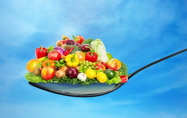 Spoon full of various fruit and vegetables on blue sky