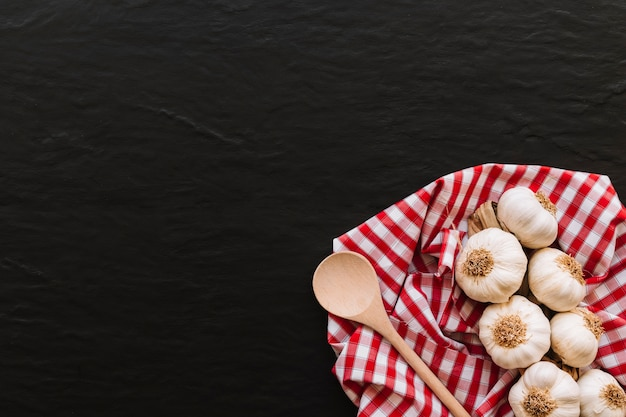 Spoon and garlic on napkin