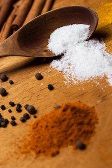 Spoon and heap of spices on the table
