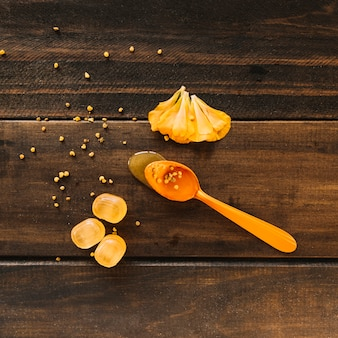 Spoon of honey near flower petals and candies on wooden background