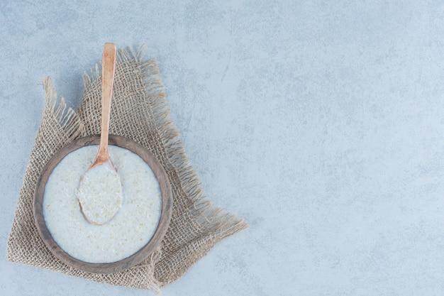 Ложка в рисовой миске, полотенце на мраморе.