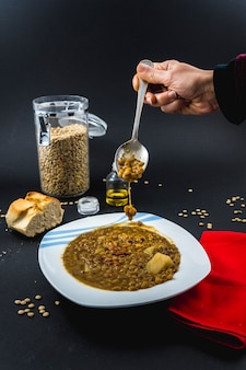 A spoon inside a plate of spanish cooked lentils