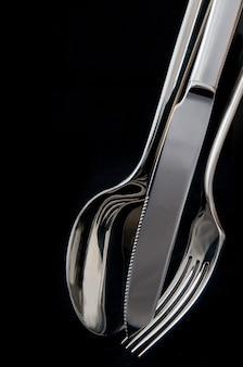 Spoon, knife and fork in black background