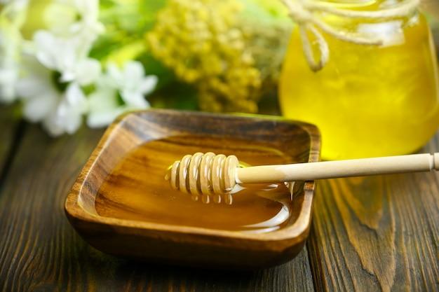 Ложка лежит в деревянной миске с медом