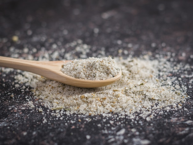 Spoon light wood on the pile of salt with herbs on a wooden table.