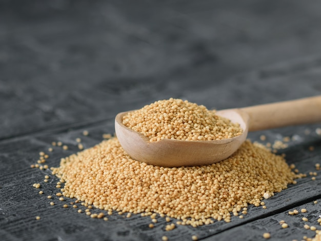 A spoon of light wood with amaranth seeds on a dakr wooden rustic table.