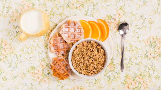 Spoon; milk pitcher and plate of healthy granola bowl with waffles and slice of an oranges over floral background