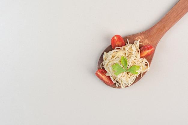 흰색 표면에 토마토 슬라이스와 파슬리 스파게티 스푼